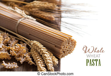 Whole wheat italian pasta with wheat spikes on wood