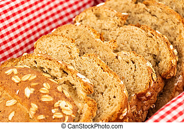 Wholegrain bread bun with oat in bowl with cloth.