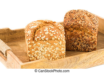 Wholegrain bread buns with seeds and oat on wooden tray on white background.