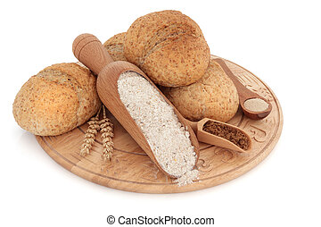 Bread roll selection on a wooden board with wholegrain flour, brown sugar and yeast in scoops, with ears of wheat, over white background..