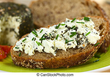 Slice of wholegrain bread spread with goat cheese with herbs with chives on top (Selective Focus, Focus on the front of the cheese)