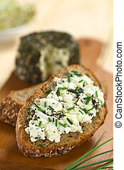 Slice of wholegrain bread spread with goat cheese with herbs with chives on top (Selective Focus, Focus one third into the cheese)