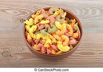 Wholegrain italian pasta in bowl on wooden background