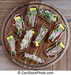 Wholegrain sandwiches with micro greens. Vegan party food table with organic vegetables canapes. Healthy lifestyle, modern cooking ingredients and eating right concept
