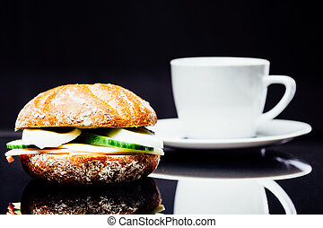 Breakfast sandwich and cup of coffee, wholegrain bread roll with cucumber, ham and egg, chees, on black background with reflection.