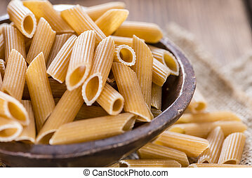 Wholemeal Pasta (Penne) as close-up shot on vintage wooden background
