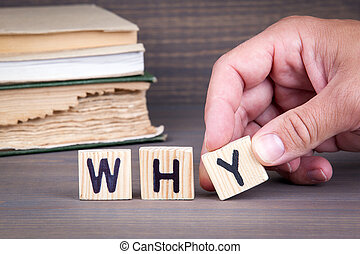 why. Wooden letters on dark background. Office desk