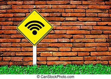 wi-fi internet traffic symbol sign on brick wall background and grass field