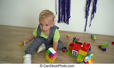 Wicked boy child play with colorful constructor bricks on...