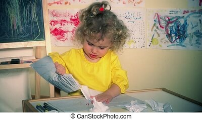 wicked child girl tearing the paper and creating a mess in the room