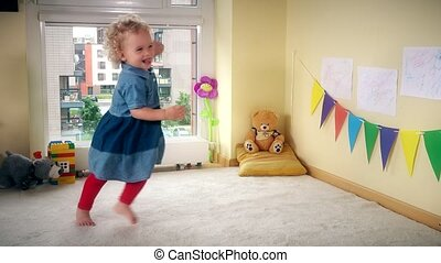 Wicked kid at home. Active girl run jump and dance with...