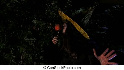 Wicked Witch with enchanted apple in Halloween Horror Scene...