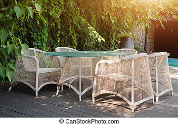 Wicker armchairs and table, modern garden furniture. Cozy space for relax in the garden.
