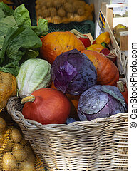 wicker basket full of colorful pumpkins and cabbage