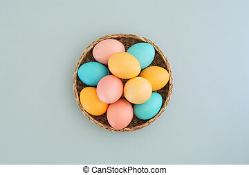 Wicker basket full of easter colorful eggs on blue background, top view, flat lay
