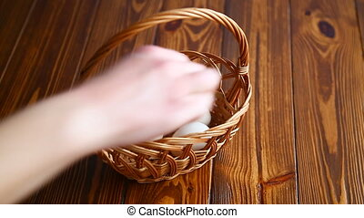 Wicker basket full with eggs on a wooden table