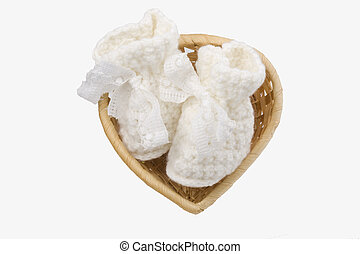 wicker basket heart-shaped with baby's bootee