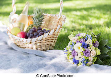 Wicker basket of fresh fruits and wedding bouquet on grass