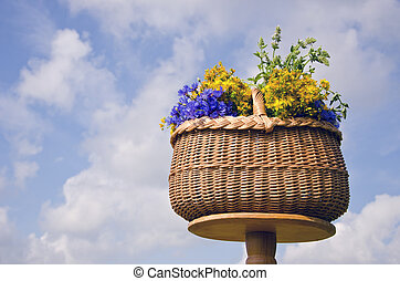 wicker basket on table with midsummer medical herb flowers