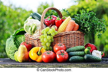 Wicker basket with assorted raw organic vegetables in the garden