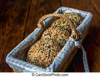 Wicker basket with bread. Bread and buns inside basket. Fresh bakery products on table. Tastes best when warm.