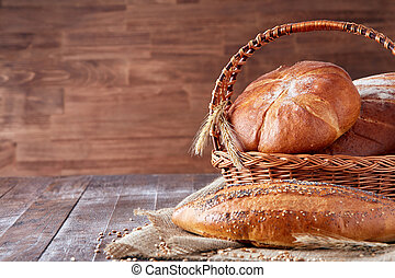 Wicker basket with bread. Bread and buns inside basket. On the wooden table.