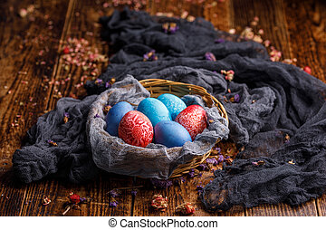 Wicker basket with colored eggs in different colors on a wooden background.