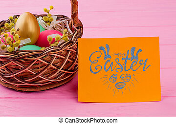 Wicker basket with colorful Easter eggs.