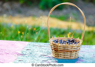 Wicker basket with dark gooseberry on bench