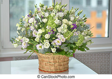 Wicker basket with flowers on the table, close-up