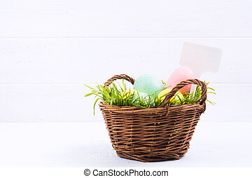 Wicker basket with green natural grass and painted pastel eggs with white label on white wooden background with copy space