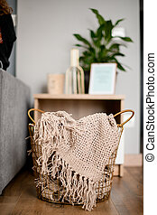 wicker basket with plaid inside standing on the floor in the room.