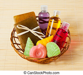 basket with soap, gel and other bath and shower accessories on bamboo mat