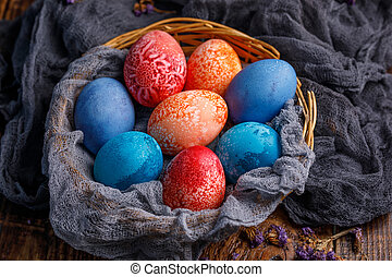 Wicker basket with unusual colored Easter eggs in different colors.