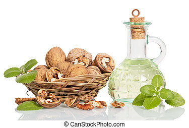 Wicker bowl with walnuts and oil bottle isolated on white.