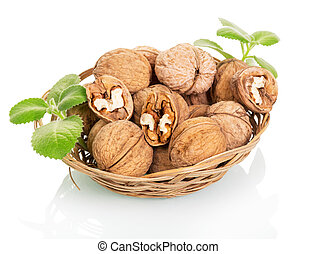 Wicker bowl with walnuts isolated on white.