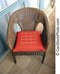 Wicker chair - Brown wicker chair with red cushion