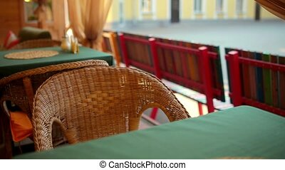 Wicker chair in an empty cafe. The camera moves dolly