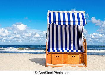 Wicker chair on sandy Kolobrzeg beach, Baltic Sea, Poland