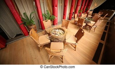 Wicker chairs and glass tables stand in a magnificent hall...