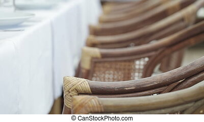 Wicker chairs - Several wicker chairs before a table covered...
