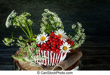 Wicker color white with red basket with a snowball, and a field of small white flowers and chamomile . Wooden background, rustic style.