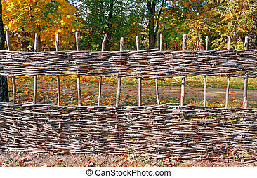 Wicker fence against the backdrop of autumn trees