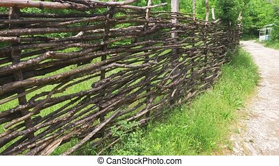 Wicker fence along the forest trail. Steadicam Shot, 4k,...
