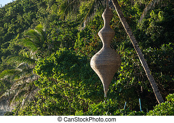 Wicker lamp in the form of flask hanging on a tree.