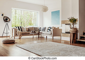 Wicker ottoman and an industrial floor lamp in a bright living room interior with chic decor and wooden elements