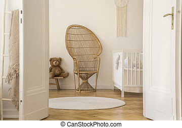 Wicker peacock chair standing in white baby room interior with crib, teddy bear and round rug on herringbone parquet in the real photo