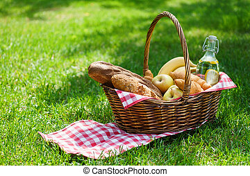 Wicker picnic basket with food and drink in a park.