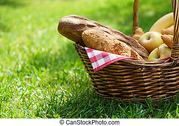 Wicker picnic basket with food on green grass.