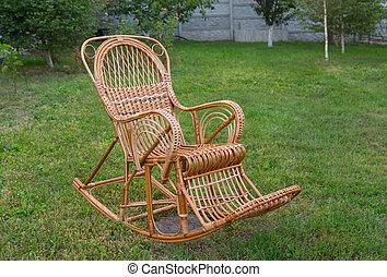 Wicker rocking-chair in the garden